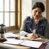 Young Hispanic woman studying near windows