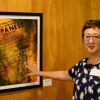 Artist Michi Takemoto stands by one of her pieces, on display at First United Methodist Church through August. Takemoto's series includes oil paintings inspired by photos of the Japanese Relocation during World War II. Photo by Richard DuPertuis.
