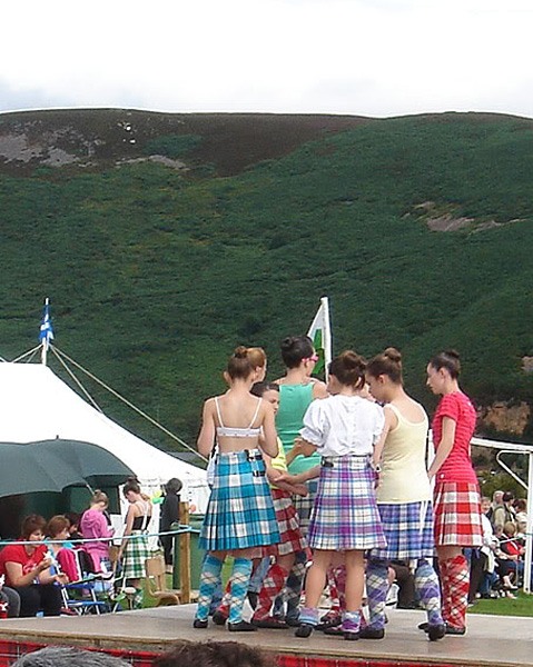 Colorful Highland dancers on Games Day.  Look higher, way up on the hill... see those two bright white rocks?  Jimmy's handiwork!