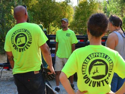 Surrounded by emblematic yellow shirts, Shasta Support Service co-founder Dale Ball (center) consults with volunteers near the end of the work day. He and his neighbor, Michael Roberts, joined in cleanups around Redding before forming their own community service group, about a year and a half ago.