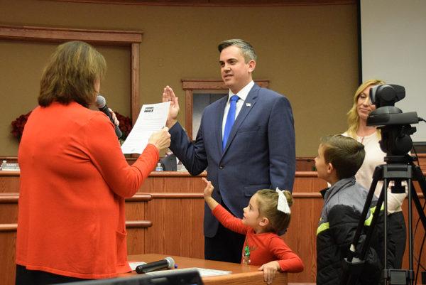 Councilman-elect Adam McElvain is sworn in as daughter, Pepper, and son, Rook, help.