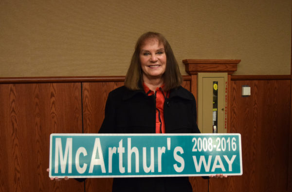 Outgoing Mayor Missy McArthur with a sign presented by Public Works Director Brian Crane.