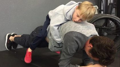 Kyle Stewart's son chills on on his dad's back while Kyle does a 90-second plank.