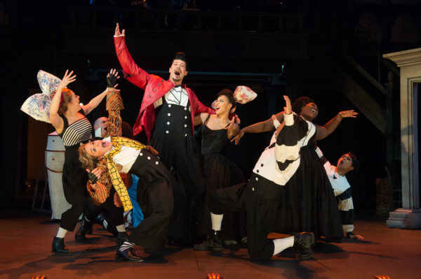 Gaston (James Ryen, center) is serenaded and cheered on by the ensemble, including LeFou (Sara Bruner), wearing the yellow scarf. Photo by Jenny Graham, Oregon Shakespeare Festival.