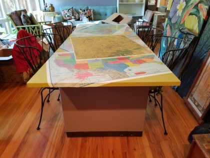 Former conference table cut down for a dining table, covered in maps. 50