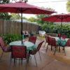 two glass patio tables four red chairs and red umbrellas - 75 per set