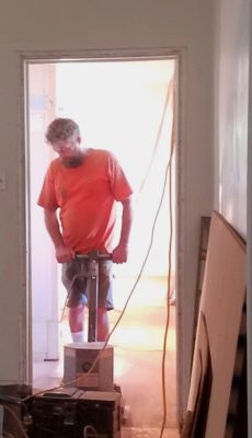 Corey Bunton sanding the back bedroom floor.