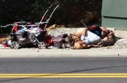 A woman sleeps with her belongings in the dirt off Pine Street in Redding. Photo by Doni Chamberlain