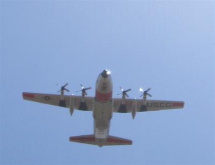 A Coast Guard C-130 flies over Friday\'s ceremony
