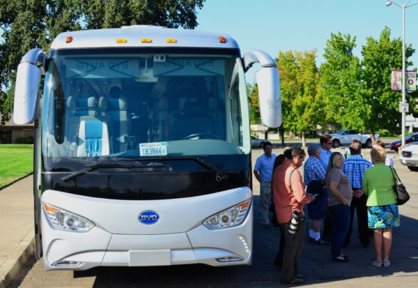 Early passengers gather in the shade before touring Redding in a long-range, all-electric bus. Photos by Richard DuPertuis.