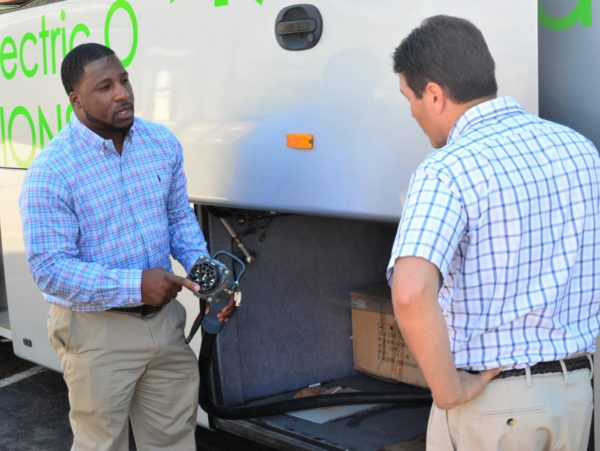 """BYD Service Manager Victor Watkins shows a passenger the """"gun"""" used to connect the bus to a charger."""