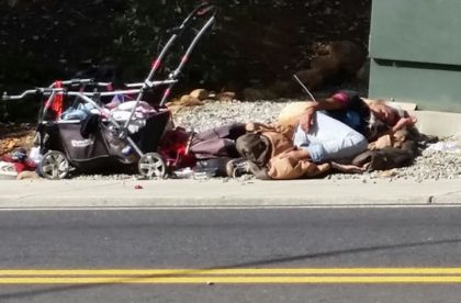A woman sleeps on the sidewalk near the East and South street intersection one recent weekday morning. Photo by Doni Chamberlain