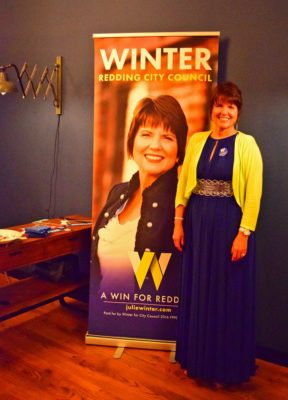 Councilwoman-elect Julie Winter poses with a campaign poster.