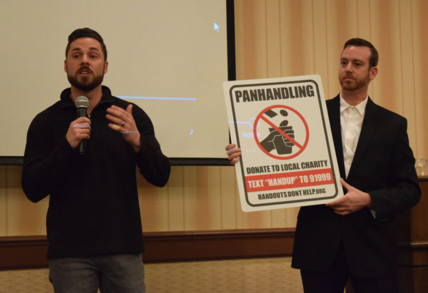 Jonathan Anderson, left, and Matt Morgan show new anti-panhandling street signs intended to funnel support to the Good News Rescue Mission.