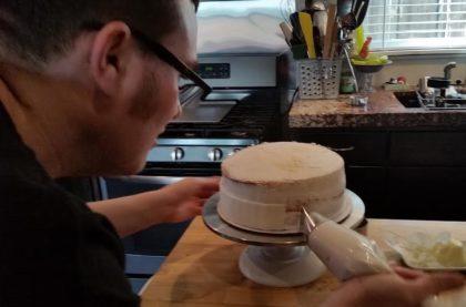 Joe applies frosting to a white wedding test cake.
