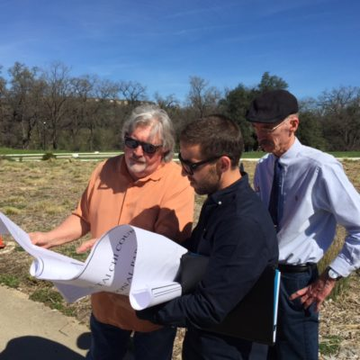 Left to right, architects Terry Topolski and Ryan Russell, with Michel Czehatowski, look at the project plans at the site location.