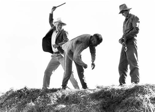 Captain, played by Strother Martin in the classic film Cool Hand Luke and shown here swinging a truncheon, knew all about crime rates and failures to communicate. Publicity photo from film.