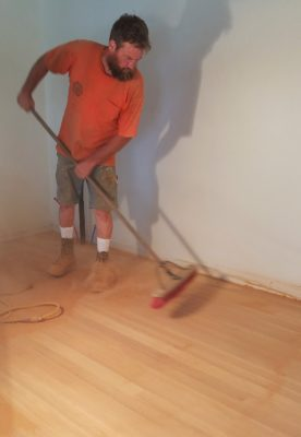 Corey sweeps between sanding layers.