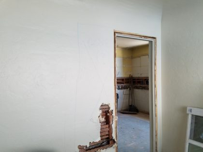 The dining room doorway will be widened. (That's the cabinet-less kitchen in the background.)
