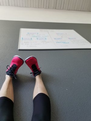 Doni does a hamstring stretch on her back (that's the ceiling above her, and the workout assignment on the wall) , and she may or may not be checking messages to see how the house is coming along.